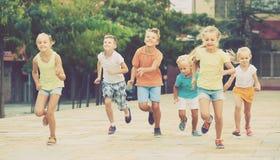 Groupe d'enfants de sourire courant ensemble dans la ville l'été Photos libres de droits
