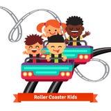 Groupe d'enfants de sourire montant des montagnes russes Image stock