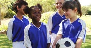 Groupe d'enfants de sourire se tenant avec le football banque de vidéos