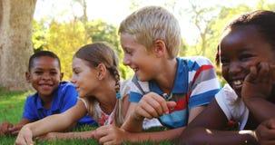 Groupe d'enfants de sourire se trouvant sur l'herbe banque de vidéos