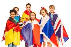 Groupe d'enfants enveloppés dans les drapeaux européens de nations Image stock