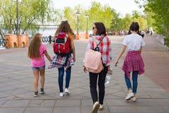 Groupe d'enfants et de femmes marchant en parc Fond urbain, rivière, ciel Vue arrière Photographie stock libre de droits