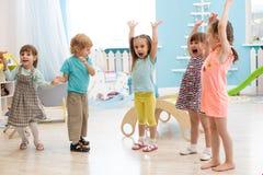 Groupe d'enfants expressifs avec soulever des mains tout en ayant l'amusement au centre de divertissement image libre de droits