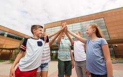 Groupe d'enfants faisant la haute cinq à la cour d'école Photo libre de droits