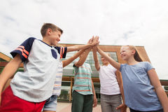 Groupe d'enfants faisant la haute cinq à la cour d'école Image libre de droits