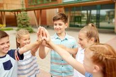 Groupe d'enfants faisant la haute cinq à la cour d'école Photographie stock