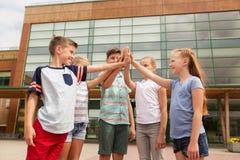 Groupe d'enfants faisant la haute cinq à la cour d'école Photos libres de droits
