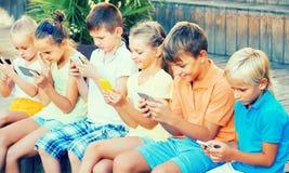 Groupe d'enfants gais jouant avec des téléphones portables dehors Photos stock