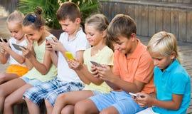 Groupe d'enfants gais jouant avec des téléphones portables dehors Photographie stock