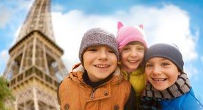 Groupe d'enfants heureux étreignant au-dessus de Tour Eiffel Photos stock