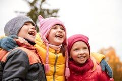 Groupe d'enfants heureux étreignant en parc d'automne Photographie stock libre de droits