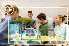 Groupe d'enfants heureux avec le PC de comprimé à l'école Photographie stock