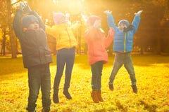 Groupe d'enfants heureux ayant l'amusement dans le parc d'automne Photo stock