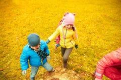 Groupe d'enfants heureux ayant l'amusement dans le parc d'automne Image libre de droits