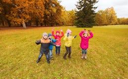 Groupe d'enfants heureux ayant l'amusement dans le parc d'automne Photo libre de droits