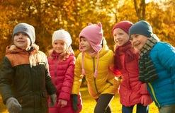 Groupe d'enfants heureux ayant l'amusement dans le parc d'automne Photos libres de droits