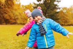 Groupe d'enfants heureux ayant l'amusement dans le parc d'automne Images stock