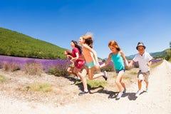 Groupe d'enfants heureux courant dans le domaine de lavande Photo stock