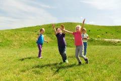 Groupe d'enfants heureux courant dehors Photos stock