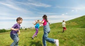 Groupe d'enfants heureux courant dehors Image stock