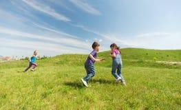 Groupe d'enfants heureux courant dehors Images stock