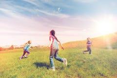 Groupe d'enfants heureux courant dehors Photo stock
