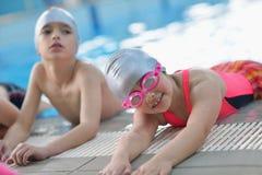 Groupe d'enfants heureux d'enfants à la piscine Photos stock