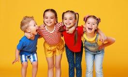 Groupe d'enfants heureux gais sur le fond jaune color? photographie stock