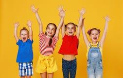Groupe d'enfants heureux gais sur le fond jaune color? images stock