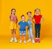 Groupe d'enfants heureux gais sur le fond jaune color? photo stock
