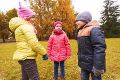 Groupe d'enfants heureux parlant en parc d'automne Image stock