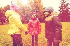 Groupe d'enfants heureux parlant en parc d'automne Photo libre de droits