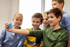 Groupe d'enfants heureux prenant le selfie avec le smartphone Photo libre de droits