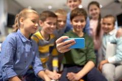 Groupe d'enfants heureux prenant le selfie avec le smartphone Photographie stock
