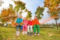 Groupe d'enfants heureux s'asseyant sur l'hamac en parc Photographie stock libre de droits
