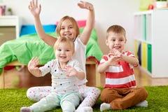 Groupe d'enfants heureux s'asseyant sur le plancher à la maison Photographie stock