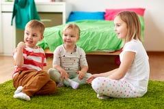 Groupe d'enfants heureux s'asseyant sur le plancher à la maison Photos libres de droits