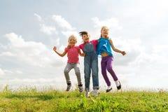 Groupe d'enfants heureux sautant haut sur le champ vert Image stock