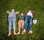 Groupe d'enfants heureux se trouvant sur l'herbe Photographie stock libre de droits