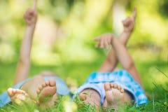 Groupe d'enfants heureux se trouvant sur l'herbe verte et le pointage Photo libre de droits