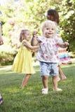 Groupe d'enfants jouant dans le jardin Photographie stock libre de droits