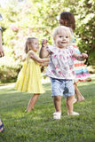 Groupe d'enfants jouant dans le jardin Photos libres de droits