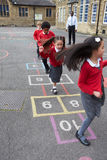 Groupe d'enfants jouant le jeu de marelle dans le terrain de jeu d'école Images stock