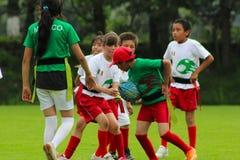 Groupe d'enfants jouant le rugby images libres de droits