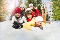 Groupe d'enfants jouant sur la neige dans l'horaire d'hiver Photo libre de droits
