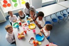 Groupe d'enfants mangeant le déjeuner dans la cafétéria de l'école photographie stock libre de droits