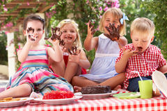 Groupe d'enfants mangeant le gâteau à la réception de thé extérieure Images libres de droits