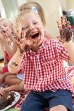 Groupe d'enfants mangeant le gâteau à la réception de thé extérieure Photo stock