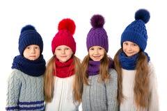 Groupe d'enfants mignons dans les chapeaux et des écharpes chauds d'hiver sur le blanc Vêtements d'hiver d'enfants Photographie stock