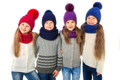 Groupe d'enfants mignons dans les chapeaux et des écharpes chauds d'hiver sur le blanc Vêtements d'hiver d'enfants Photo libre de droits